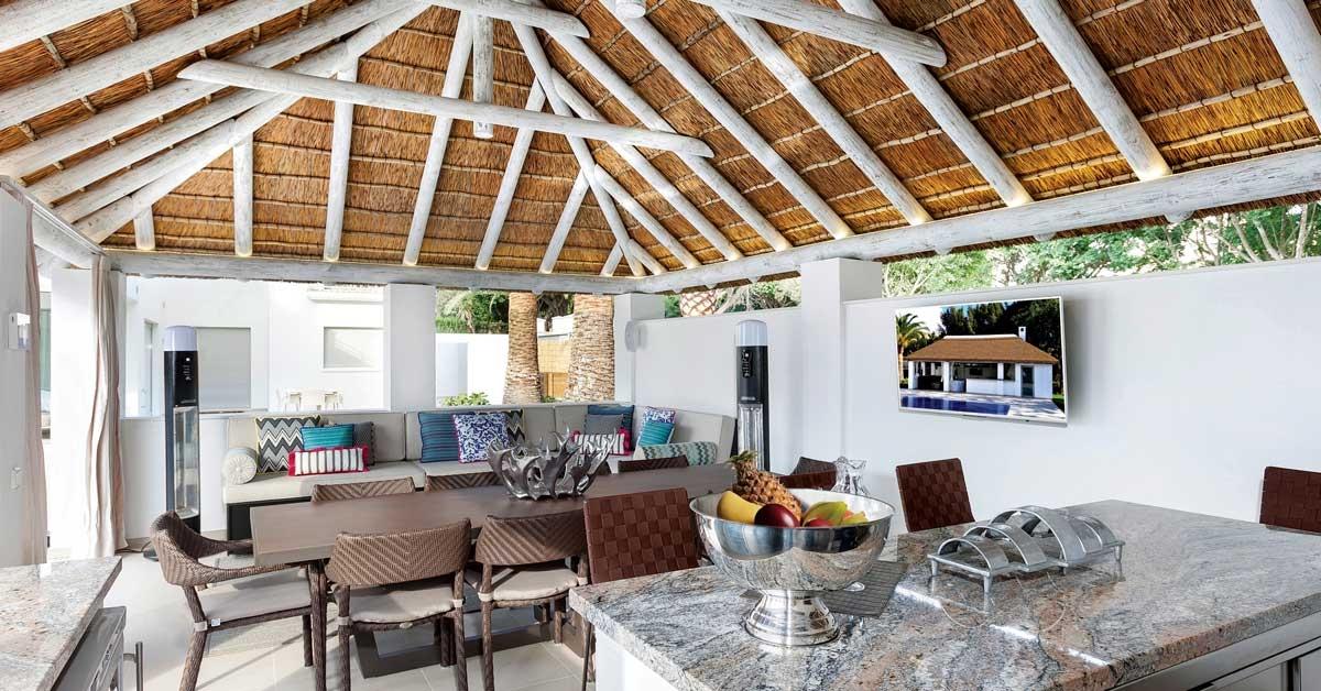 Vista interior de cenador de madera con cubierta de junco africano y vigas con acabado blanco