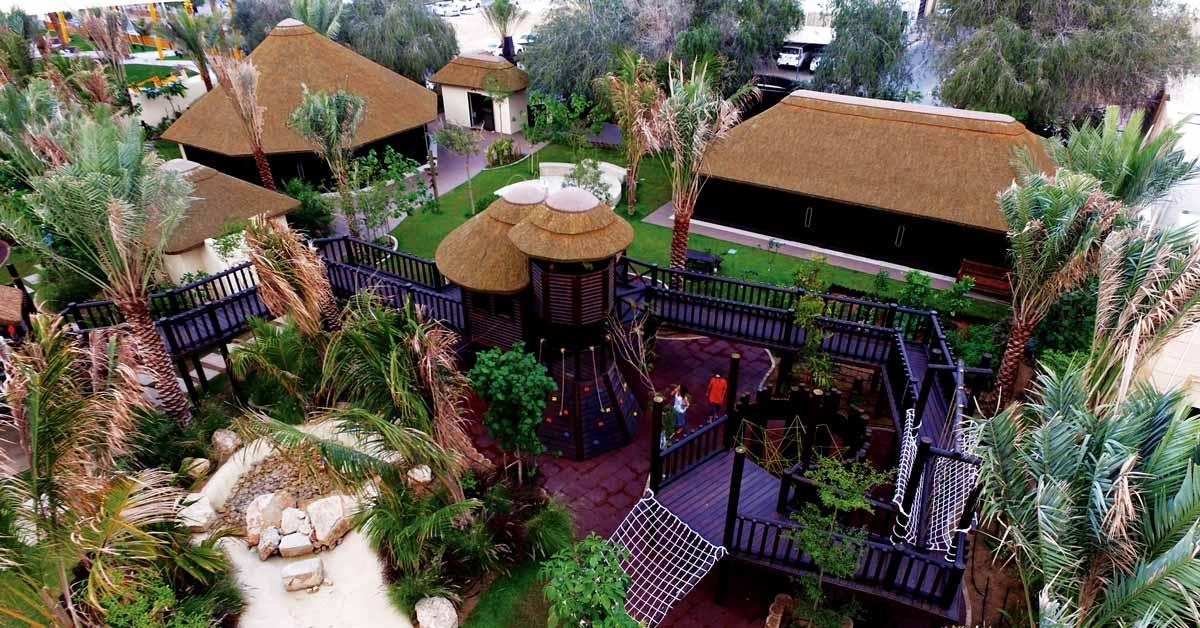 Parque de juegos con estructuras de madera y cubiertas de junco africano