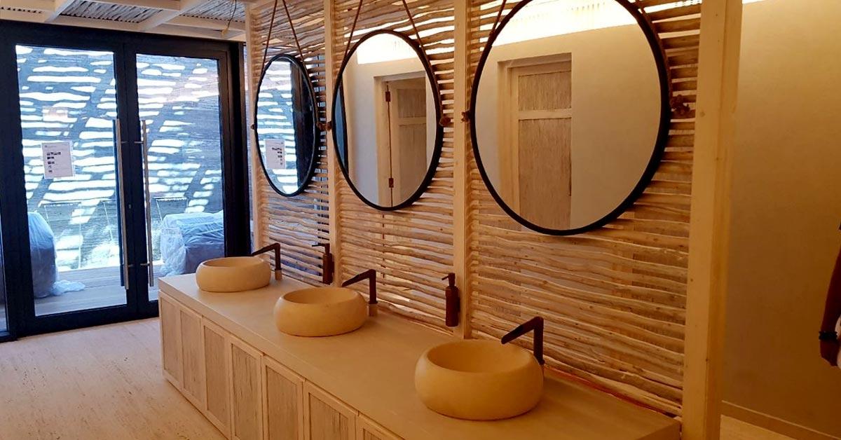 Un biombo de madera proporciona un acabado original para este baño.