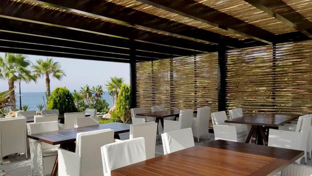 Los listones de madera proporcionan sombra y privacidad a la terraza de un chiringuito.