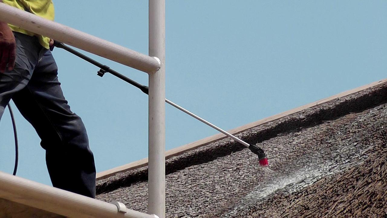 Operario rociando Cape Reed Fireshield a un techo de junco africano