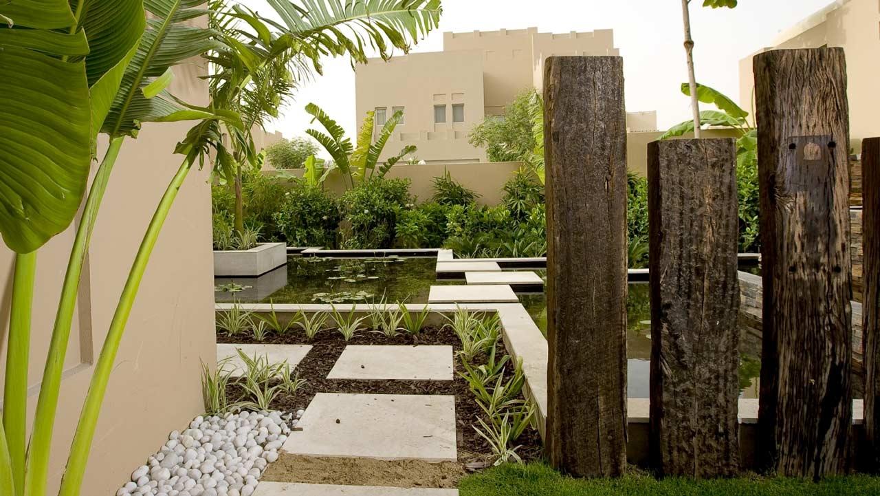 Las vigas de madera pueden ser una forma elegante de separar espacios en el jardín.
