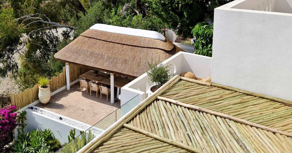 Outdoor thatched gazebo seating area with lath fence and pergola in Marbella